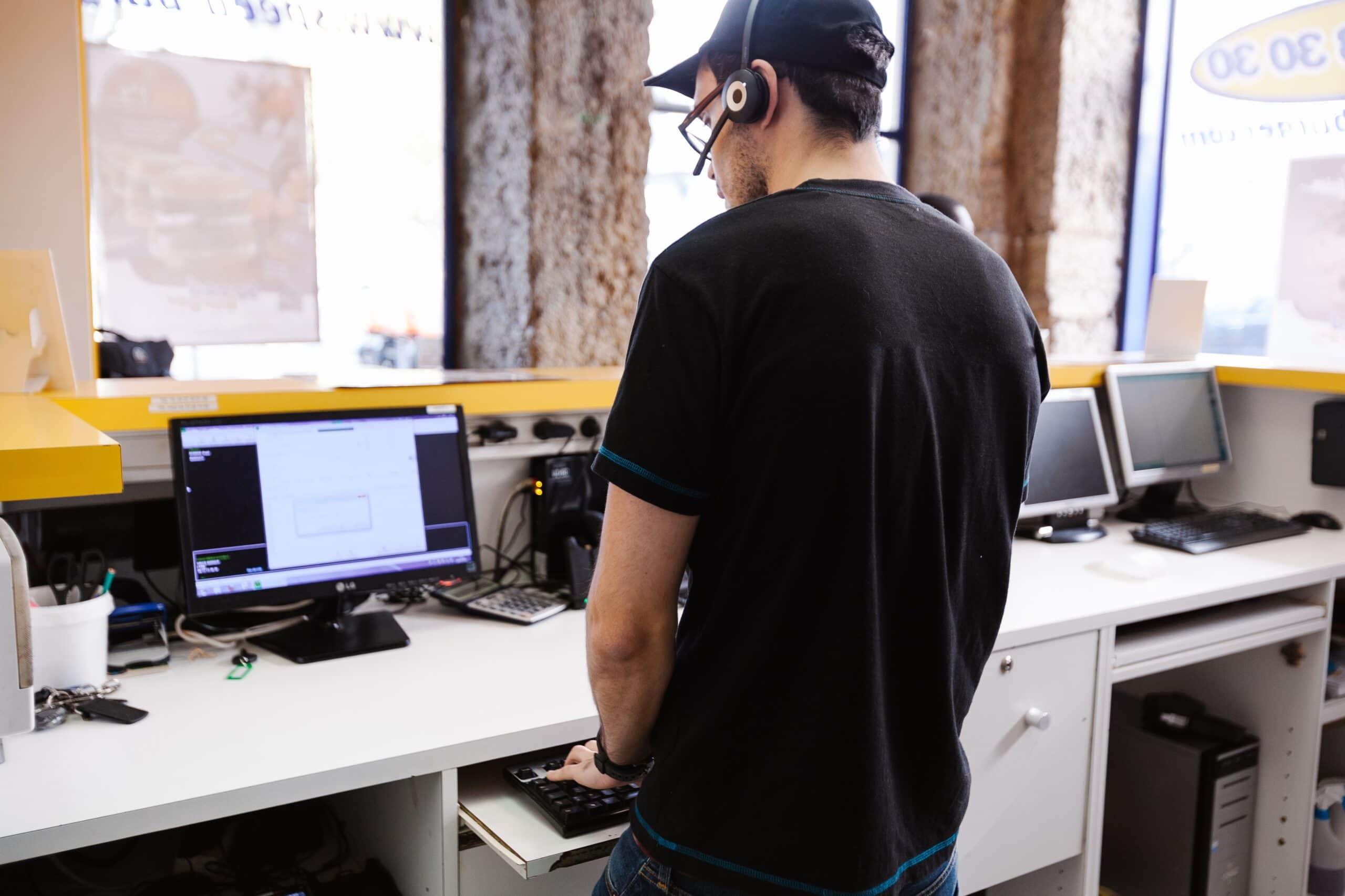 Man Working On Computer At RV Dealership