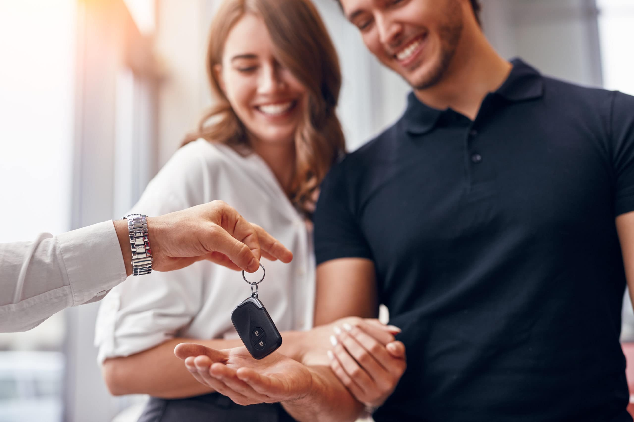 Couple Blurred In Background Smiling While Being Handed Keys To New Vehicle